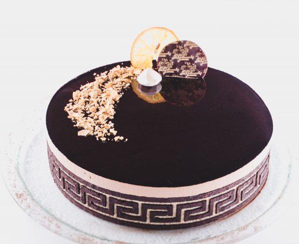 Torta Prestige ganache, čokoladna torta v sredici creme brulee pomaranča. Obdana z dekorativnim biskvitom