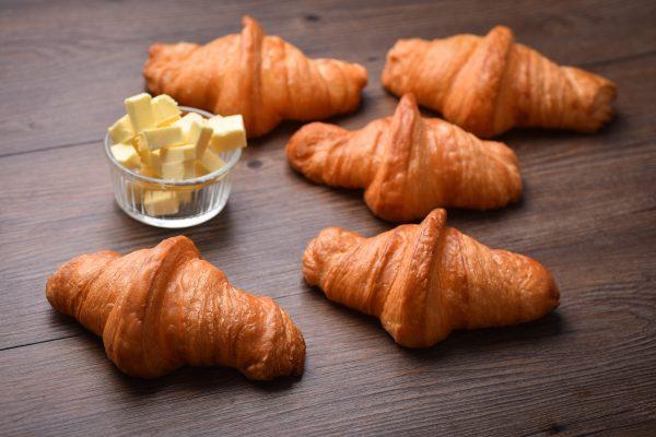 Croissant masleni rogljički 5 rogljučkov na temni podlagi. Poleg je skledica z maslom