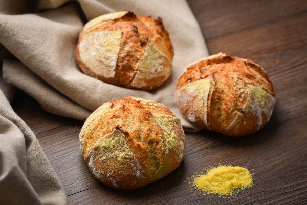 Koruzni kruh z drožmi trije hlebčki na temni podlagi